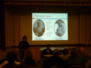 Jennifer talking about the Dunbars; on the left a picture of Albert Dunbar is seen, and Lafayette Dunbar is on the right.